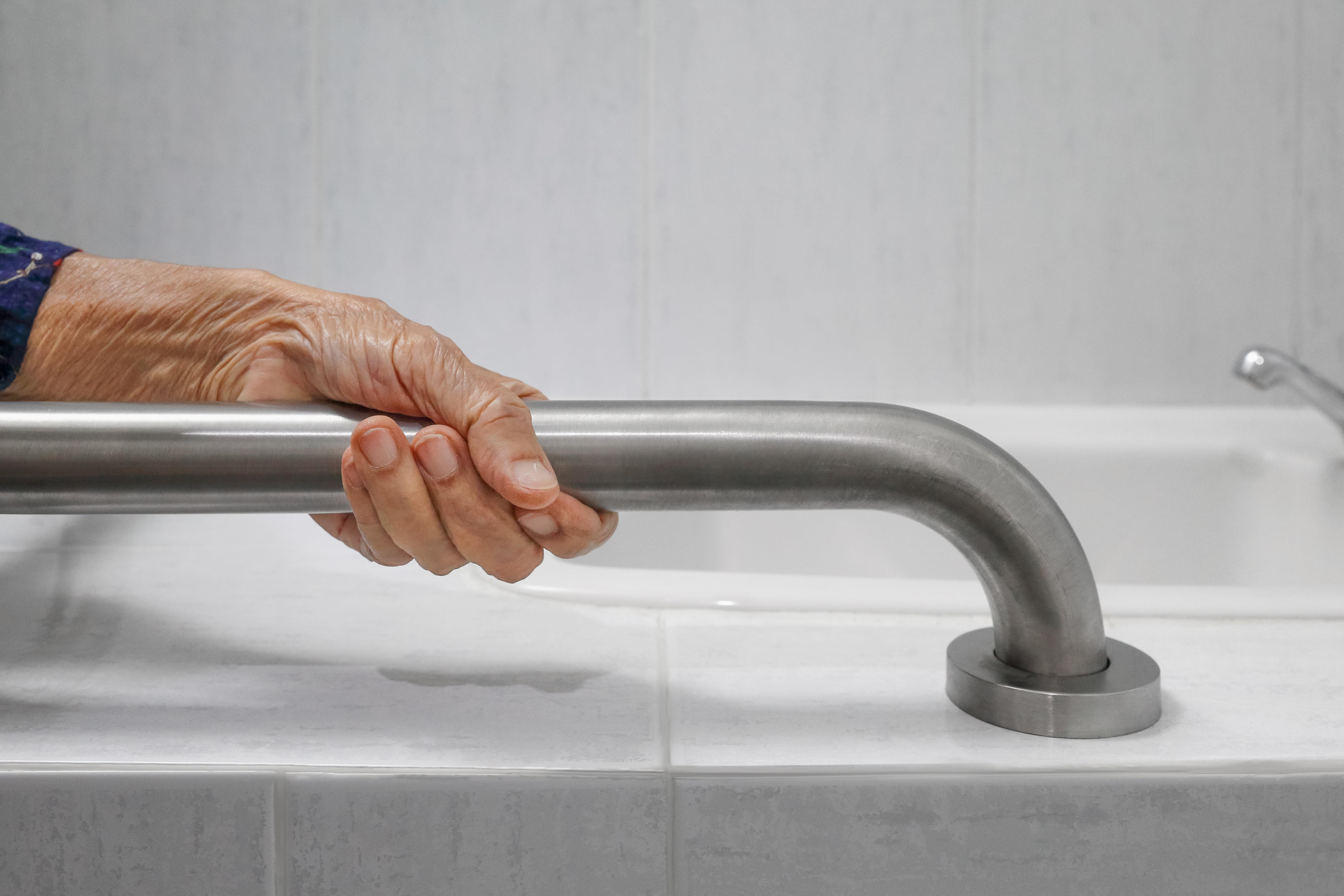 Elderly person holding on handrail in bathroom