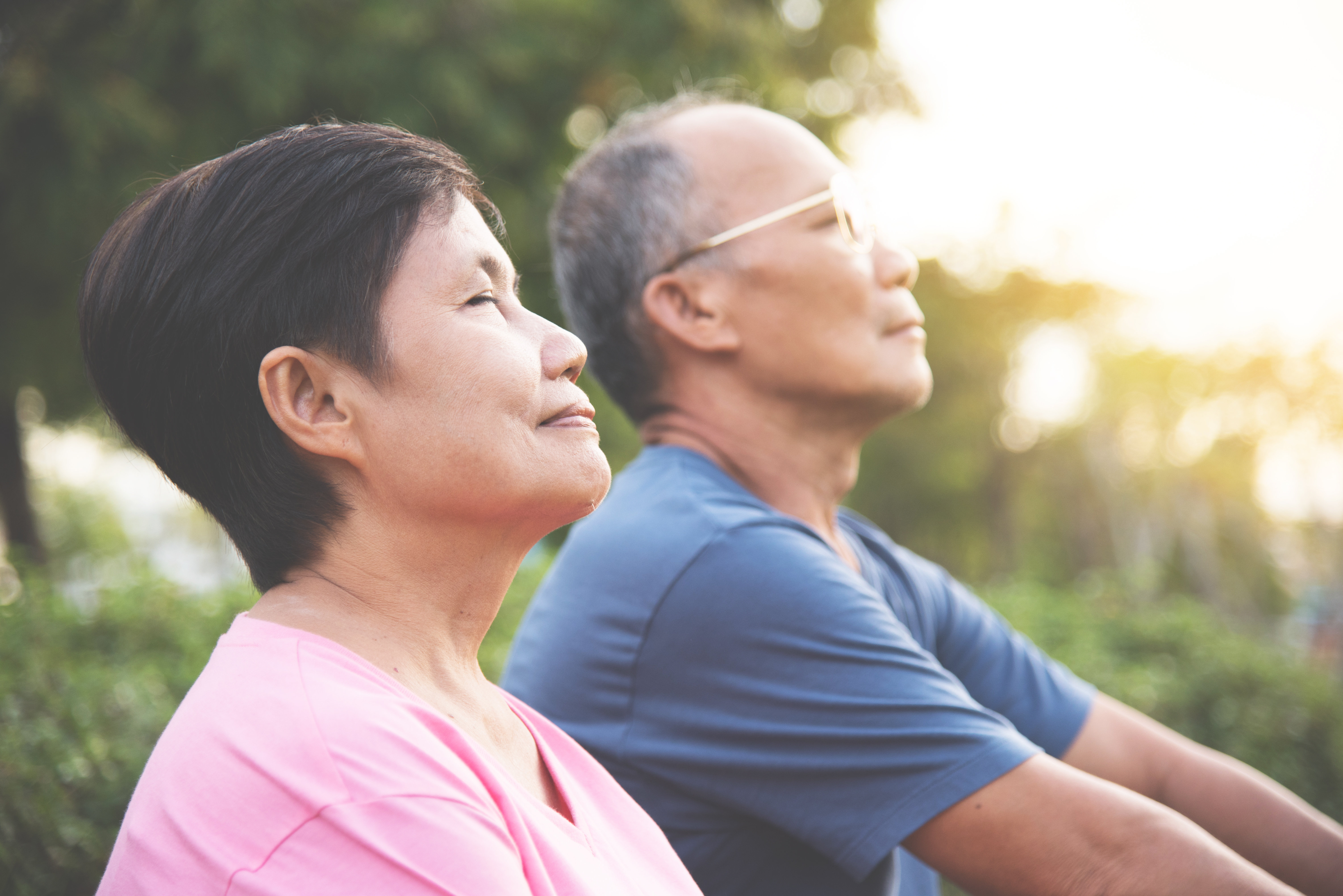 Happy Asian senior couple smiling and breathing fresh air while exercising at park outdoors