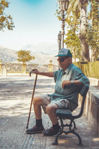 Older man with cane sitting on bench