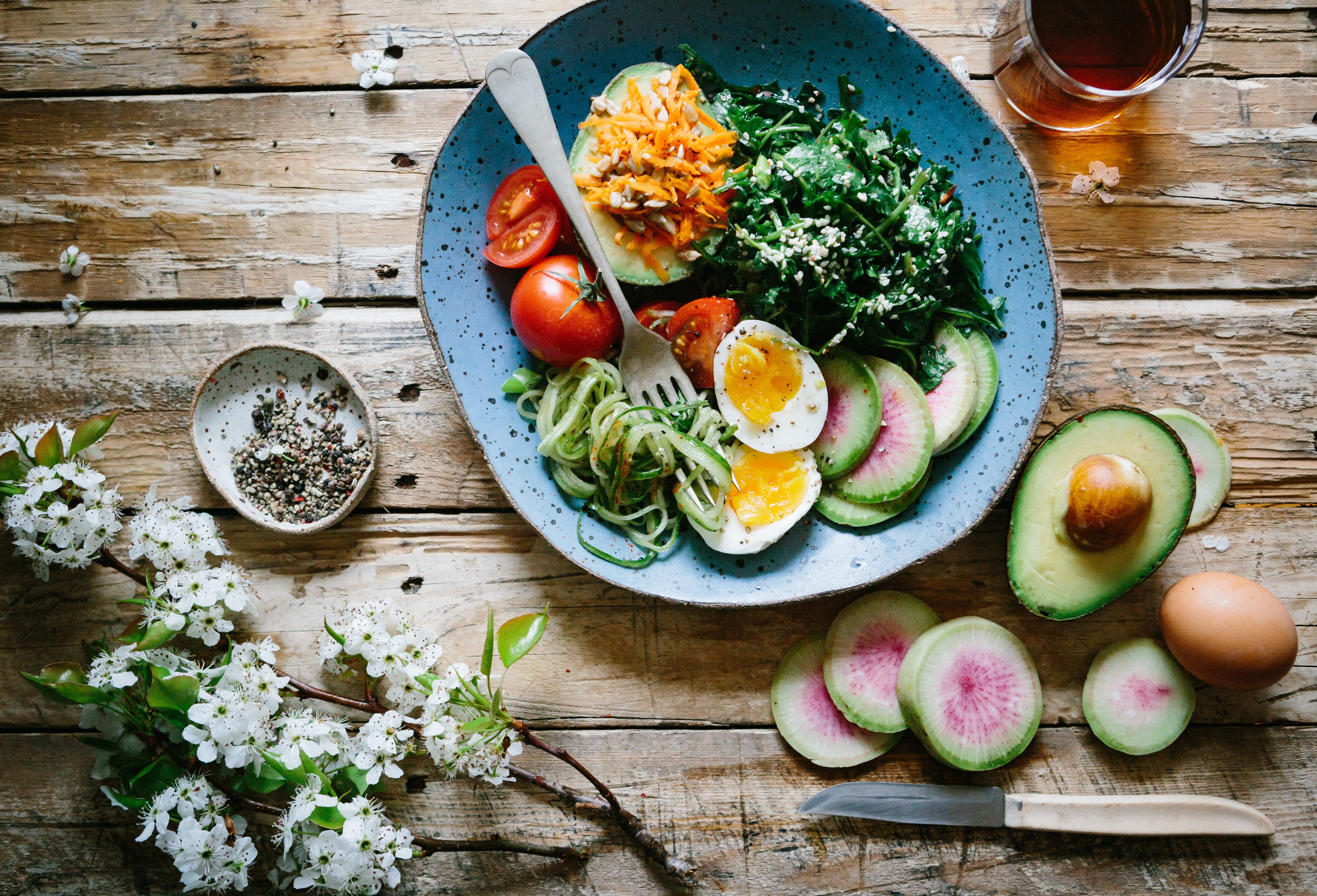 Healthy salad and flowers on wooden table
