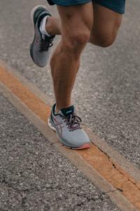 Runner's legs, wearing sneakers, running on street