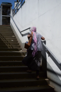 Scarved woman going up stairs