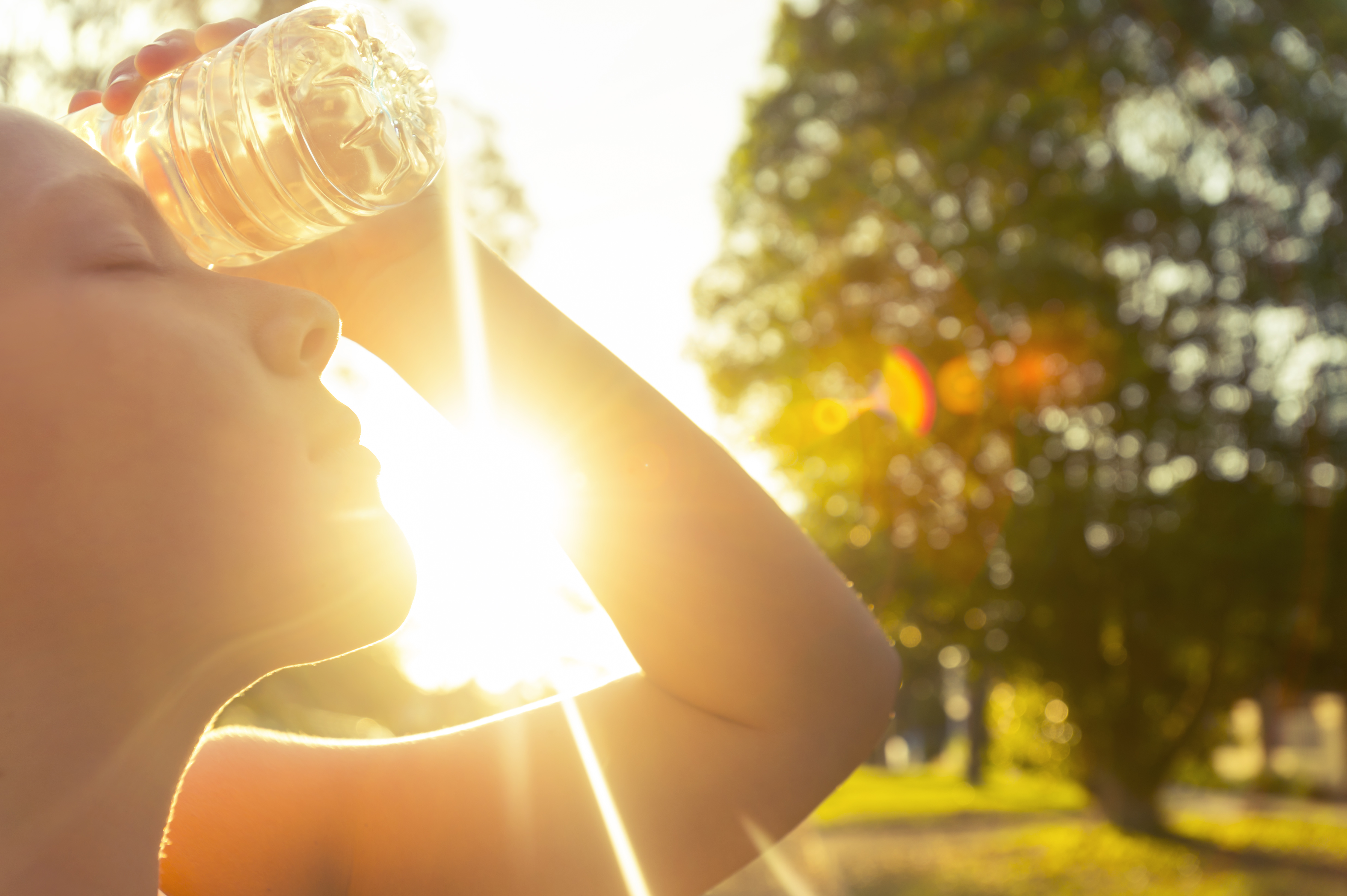 Woman using water bottle to cool down. Fitness and wellbeing concept with female athlete cooling down on a city street. She is holding a water bottle to her head to cool down. The sun is low creating long shadows and some lens flare.