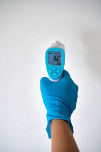 Gloved hand holding electronic thermometer