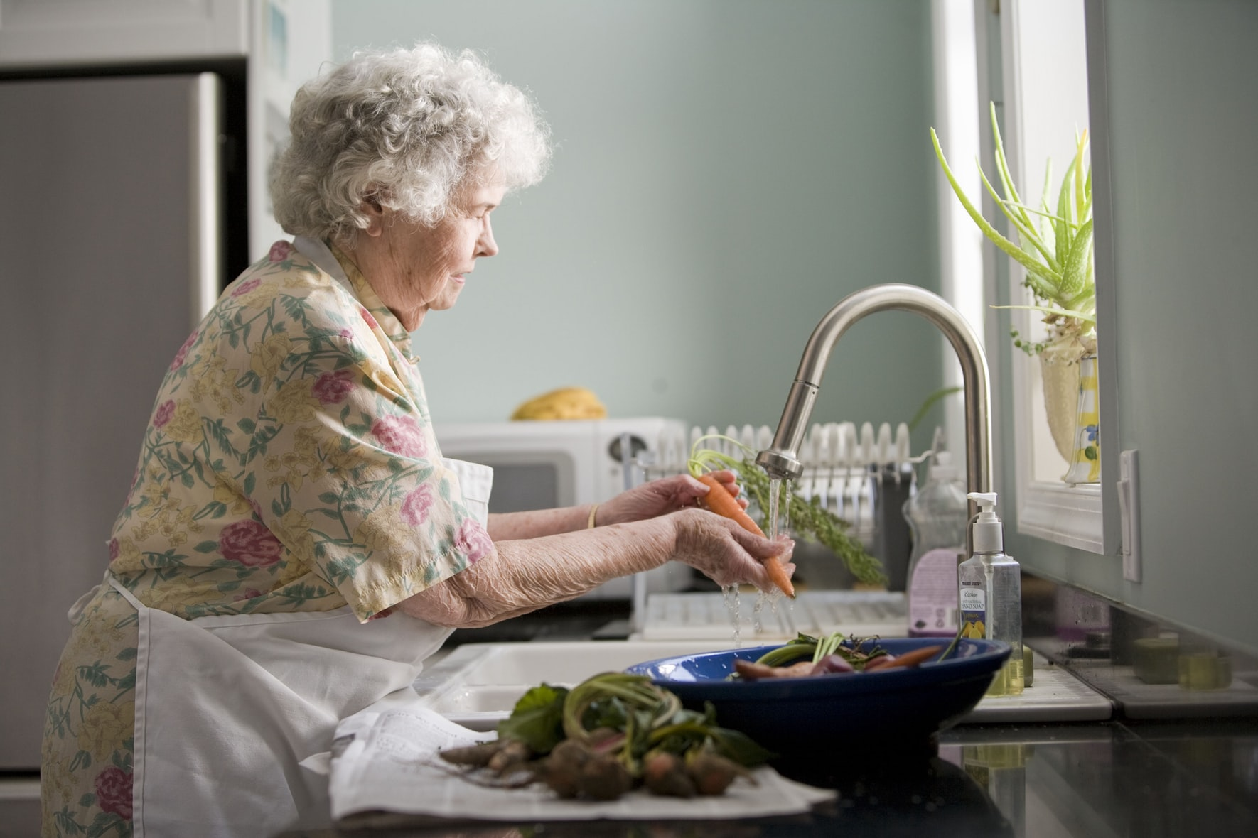 A senior woman washing carrots and other vegetables in the kitchen sink in front of the window.